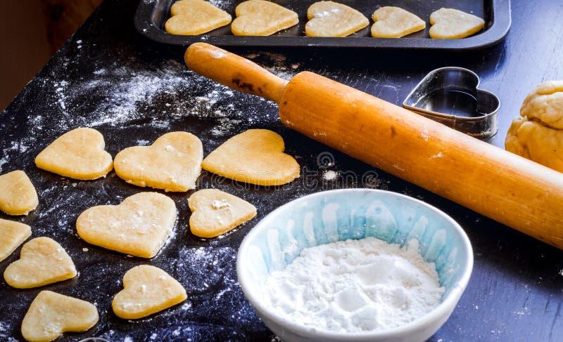 Het koken van eigengemaakte koekjes met handen op donkere achtergrond royalty-vrije stock afbeeldingen