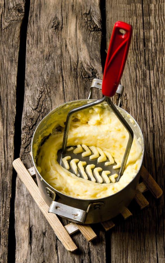 Het koken van fijngestampte aardappels met stamper op houten achtergrond stock fotografie
