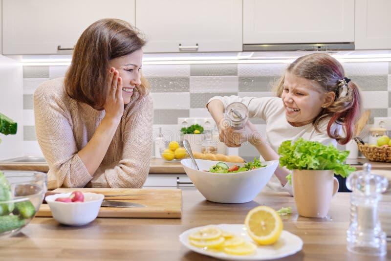 Het koken van gezonde huismaaltijd door familie Het meisje zout vers gekookte salade, kijkt de moeder omhooggaand en verheugt zic stock afbeeldingen