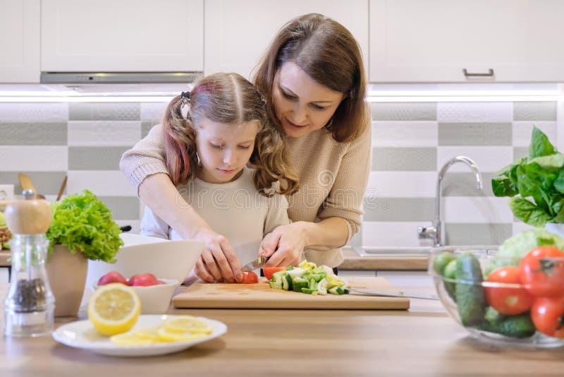 Het koken van gezonde huismaaltijd door familie Moeder en dochterbesnoeiingsgroenten thuis in de keuken voor salade stock foto's