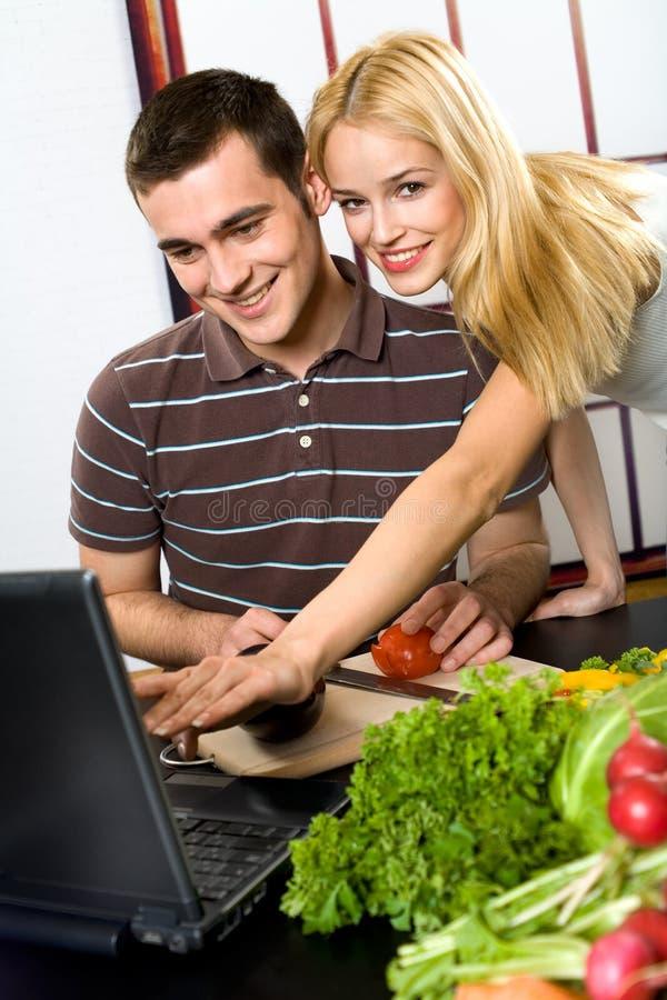 Het koken van het paar met laptop stock afbeelding