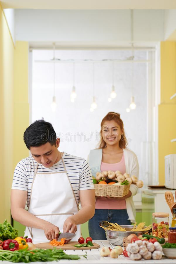 Het koken van het paar in keuken stock afbeeldingen