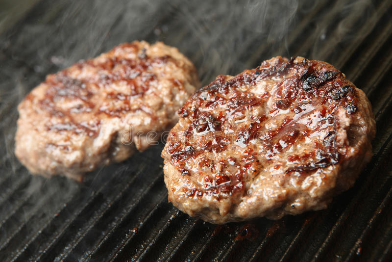 Het Koken van rundvleesburgers op Roosterplaat stock afbeelding