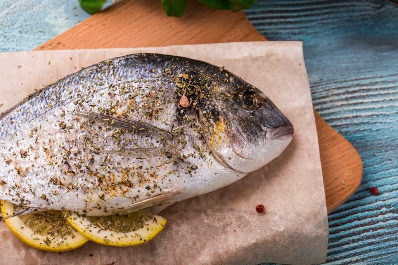 Het koken van Ruwe Dorado-Vissen met Spinazie, rozemarijn, olijven, Kruiden, Kruiden en Citroenclose-up op Houten Scherpe Raad op royalty-vrije stock foto's
