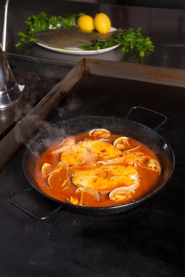 Het koken van stokvissen in cidersaus stock foto