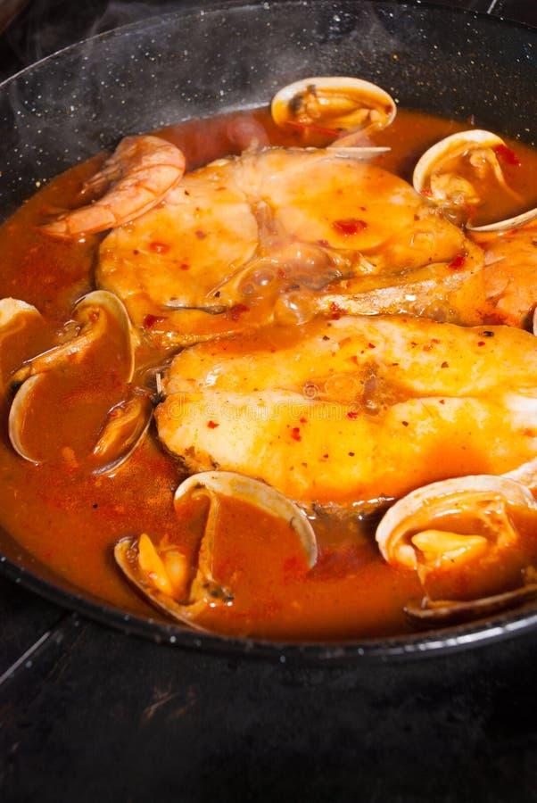 Het koken van stokvissen in saus stock foto's