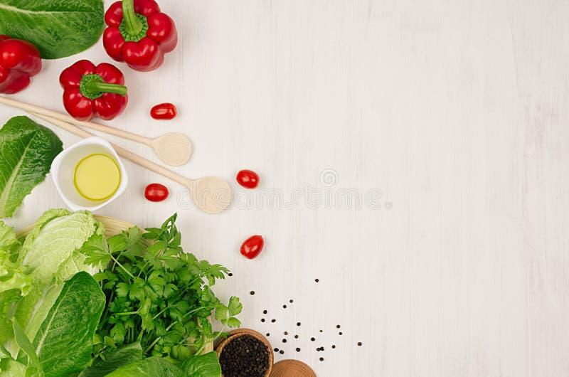 Het koken van verse de lentesalade van groene en rode groenten, kruiden op witte houten achtergrond, grens, hoogste mening stock afbeeldingen
