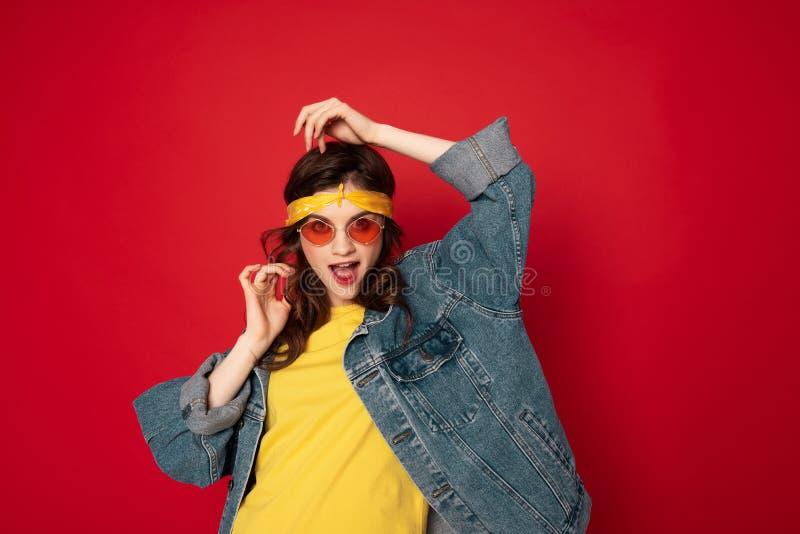 Het kokette hipstermeisje stellen ge?soleerd op rood royalty-vrije stock foto's