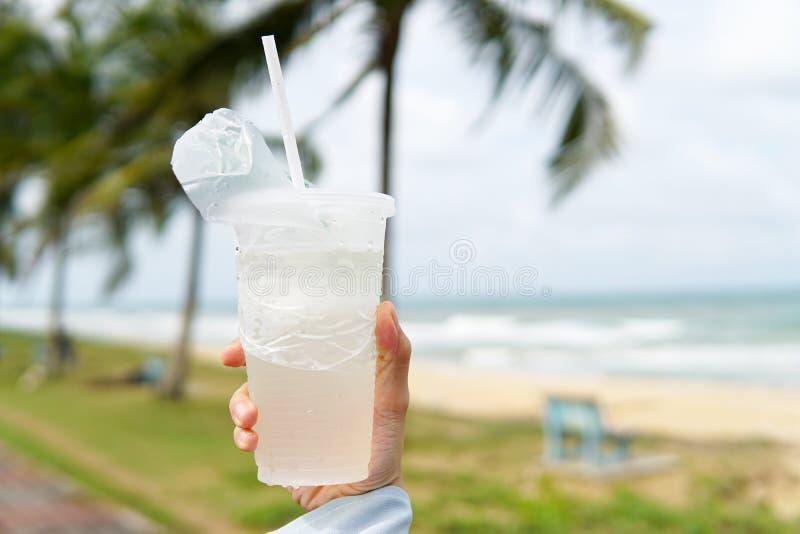 Het kokosnotensap, drinkt kokosnotenwater in transparante plastic container met strandachtergrondafbeelding stock foto's