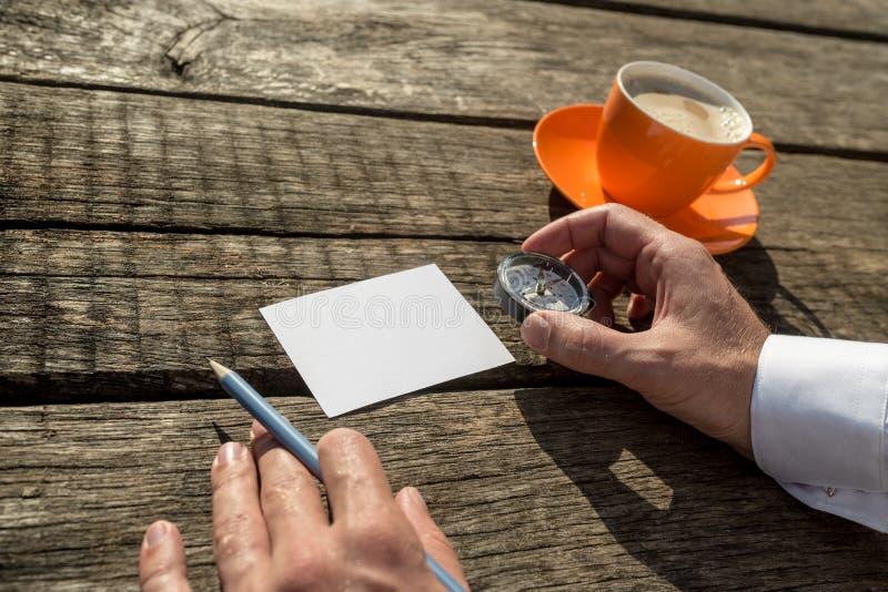 Het kompas en het potlood van de mensenholding klaar om op leeg document te schrijven royalty-vrije stock afbeeldingen