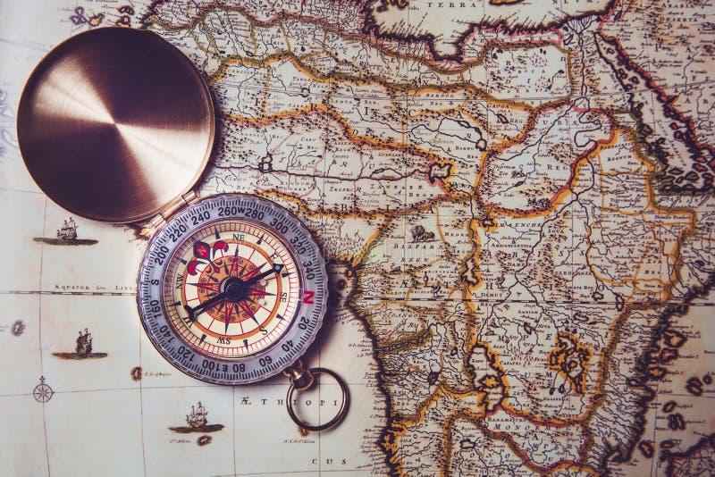 Het kompas ligt op een oude kaart Richtlijn ter plaatse door kompas stock afbeelding