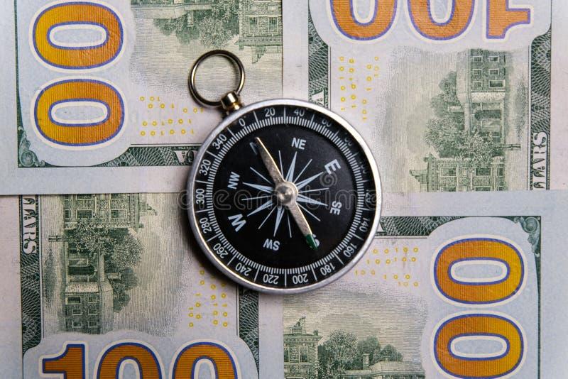 Het kompas ligt op honderd-dollar contant geldrekeningen Close-up stock fotografie