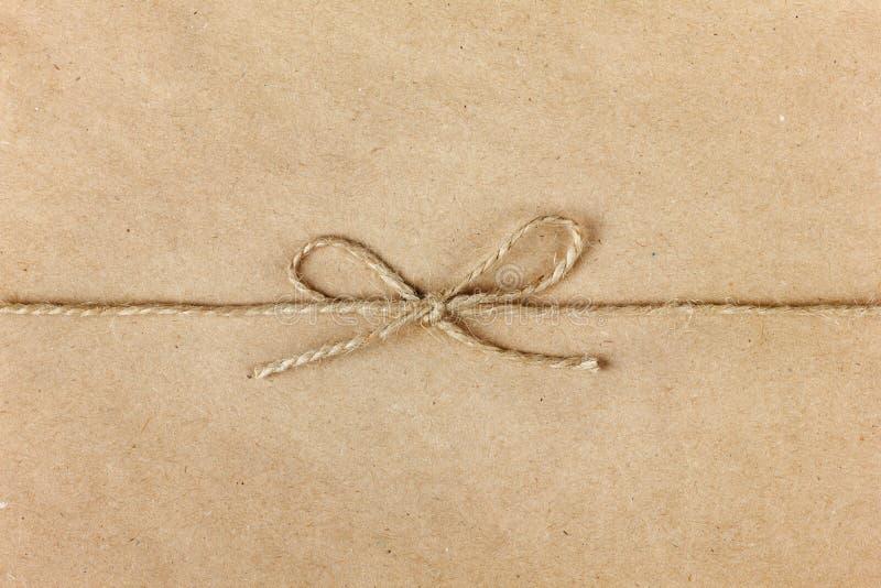 Het koord of de streng bond een boog op kraftpapier-document vast stock foto's