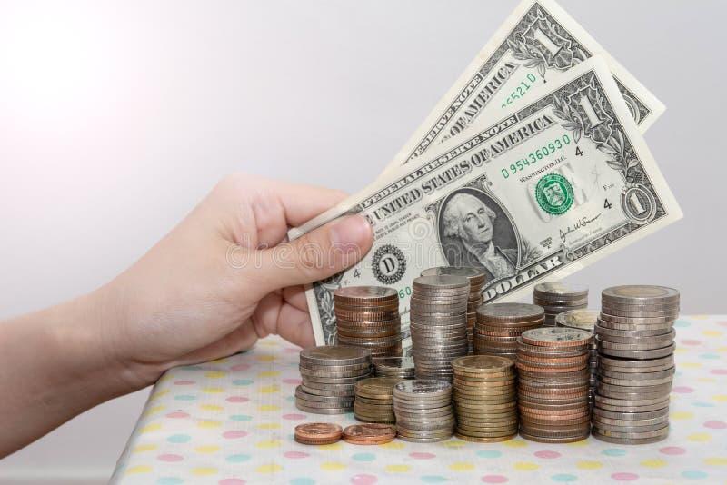 Het kopen concepten huidig door Vrouwelijke hand die bankbiljetten achter de stapels van het geldmuntstuk op wit tonen, Financiee stock fotografie