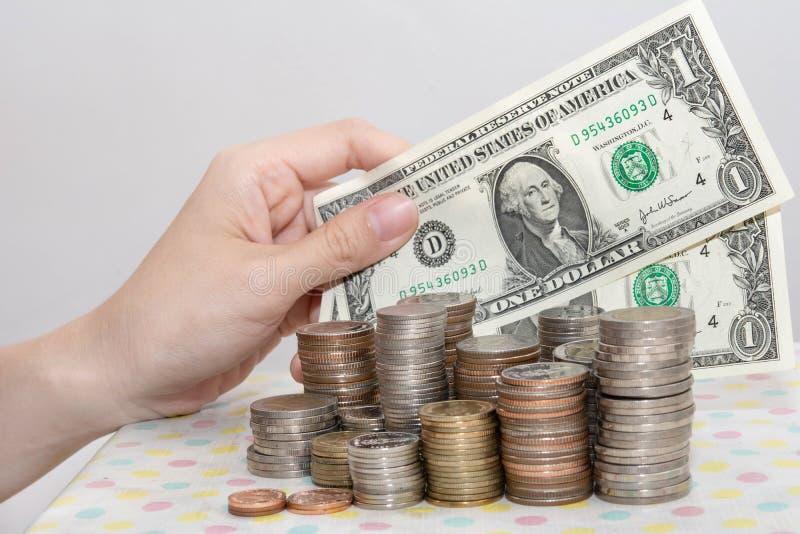 Het kopen concepten huidig door Vrouwelijke hand die bankbiljetten achter de stapels van het geldmuntstuk op wit tonen, Financiee royalty-vrije stock foto's