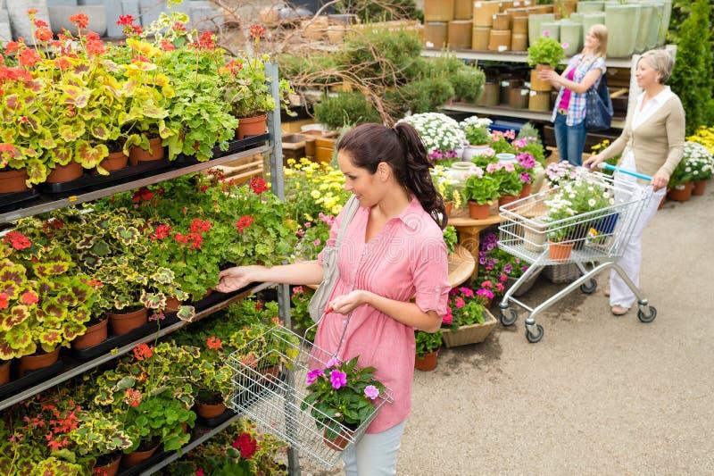 Het kopen van de vrouw ingemaakte bloem in tuincentrum stock foto