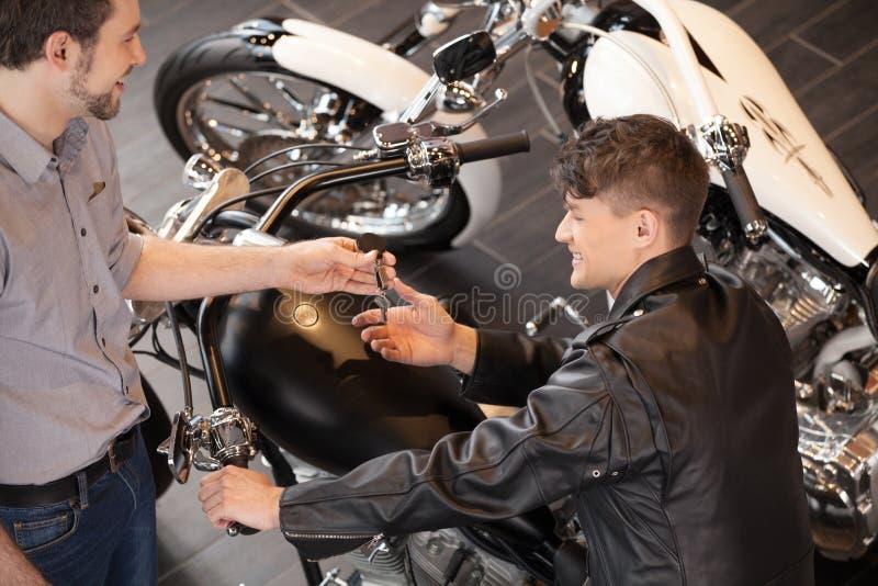 Het kopen van een motorfiets. Hoogste mening van vrolijke jonge verkoopstafmedewerker royalty-vrije stock afbeeldingen