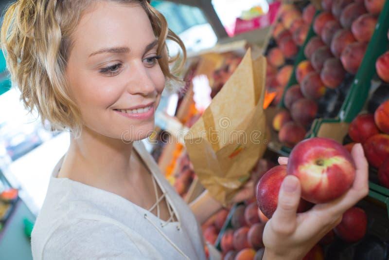 Het kopen van perziken bij landbouwersmarkt stock afbeelding