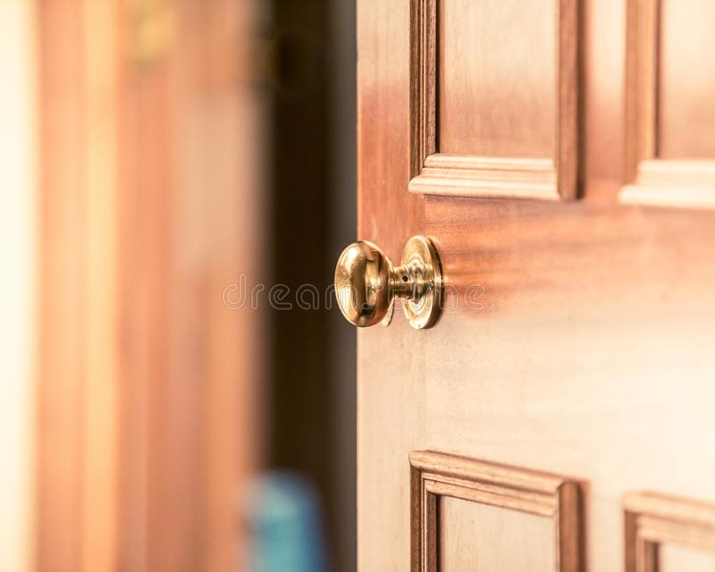 Het kopende nieuwe huis, die uw huis verkopen, uitnodigend mensen over aan uw huis, deurknop, deurhandvat, opende lichtjes houten stock afbeelding