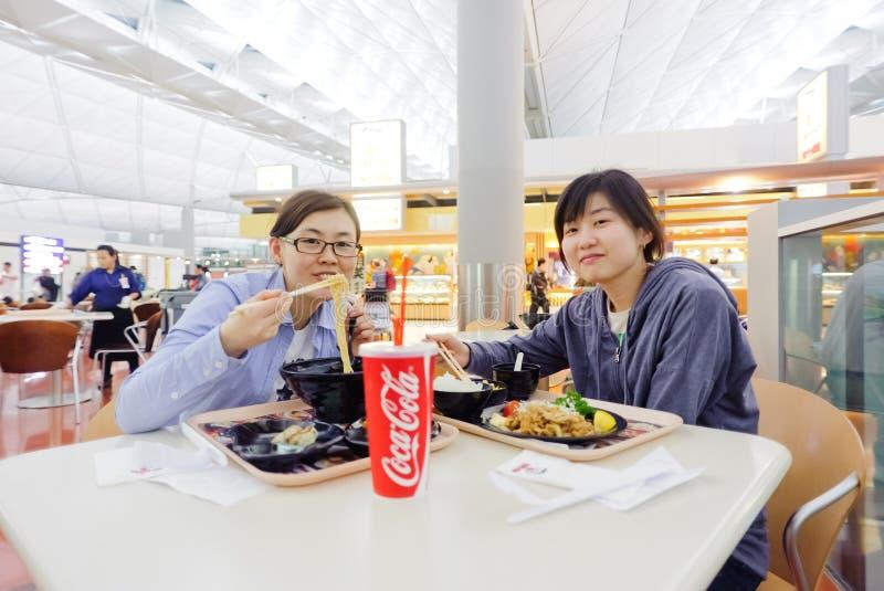 Het Koreaanse meisje eet Japans voedsel in Hong Kong International Airport stock afbeeldingen