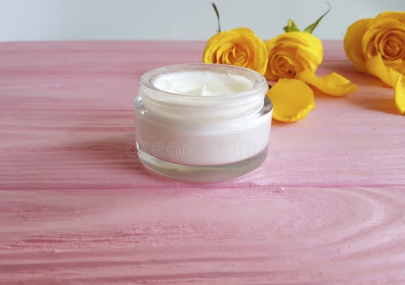 Het kosmetische room anti verouderen, geel product, nam huid careon een houten roze toe stock afbeelding