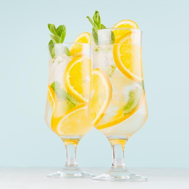 Het koude tropische sinaasappelensap misted binnen wijnglas met gesneden fruit, munt, ijsblokjes op pastelkleur zachte blauwe ach stock foto's