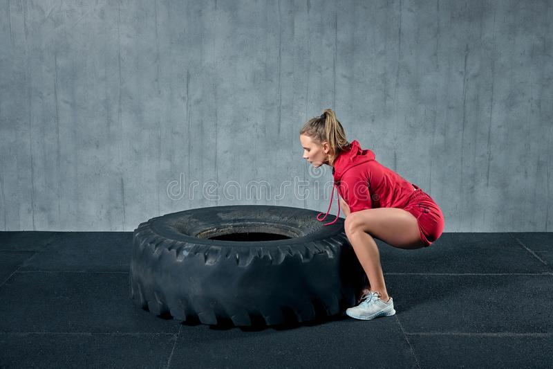 Het krachtige, aantrekkelijke spiermeisje nam in gymnastiek in dienst, opleidend met reuzebanden in de gymnastiek stock foto's