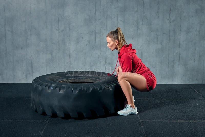 Het krachtige, aantrekkelijke spiermeisje nam in gymnastiek in dienst, opleidend met reuzebanden in de gymnastiek stock foto