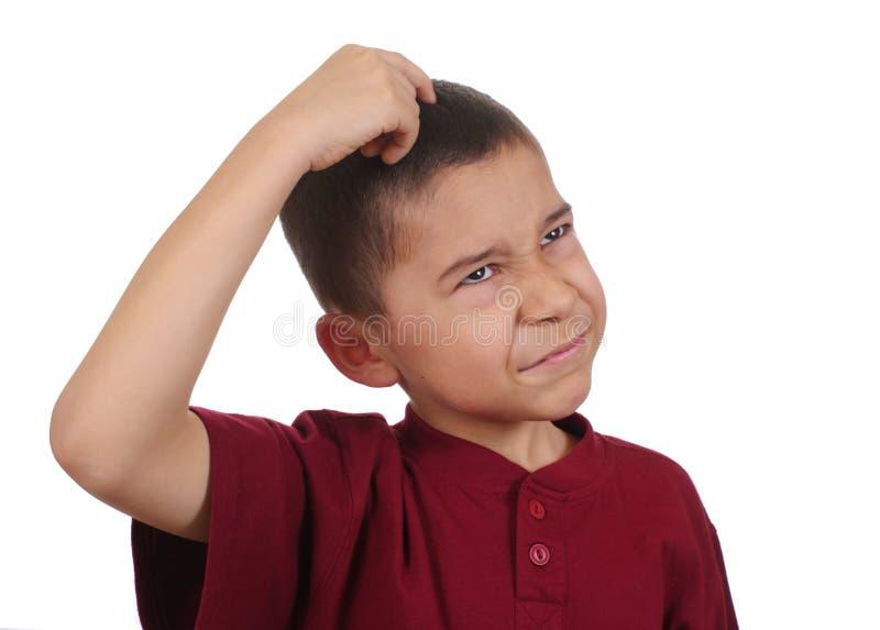 Het krassende hoofd dat van de jongen verward denkt royalty-vrije stock afbeelding