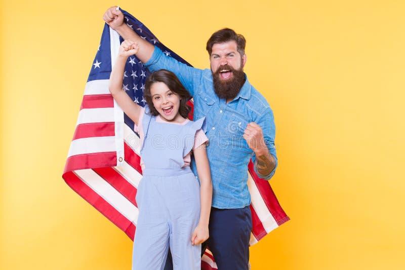 Het krijgen in de vakantiegeest Vader en klein kind die Amerikaanse vlag op nationale feestdag houden Gelukkige Familie stock afbeeldingen