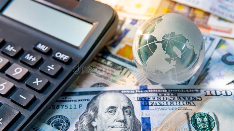 Het kristal en de calculator van de wereldbol op bankbiljetten stock fotografie