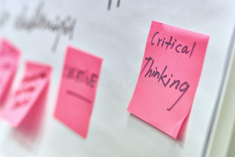 Het kritieke geschreven denken op roze document stickers in bijlage aan een tikgrafiek stock foto's