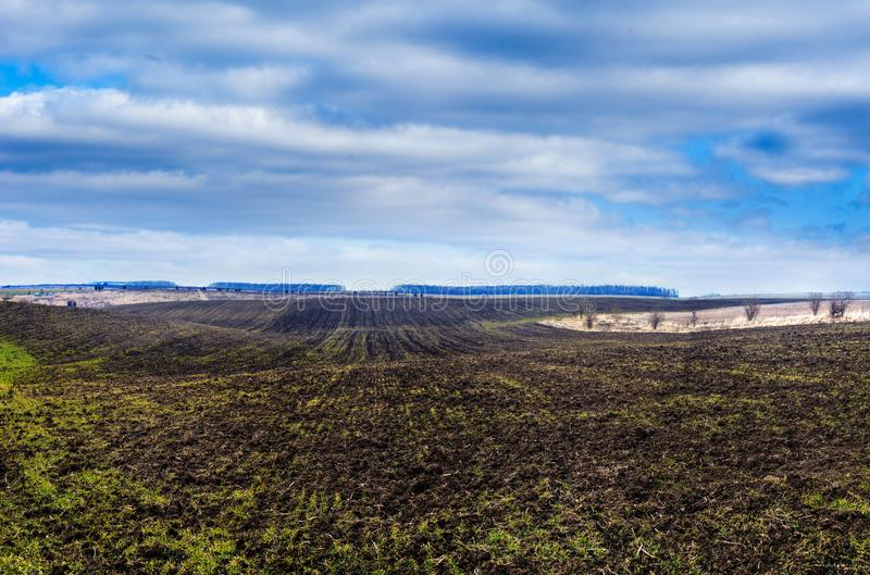 Het kronkelen van geploegd gebied in de vroege lente, wolkenhemel stock foto