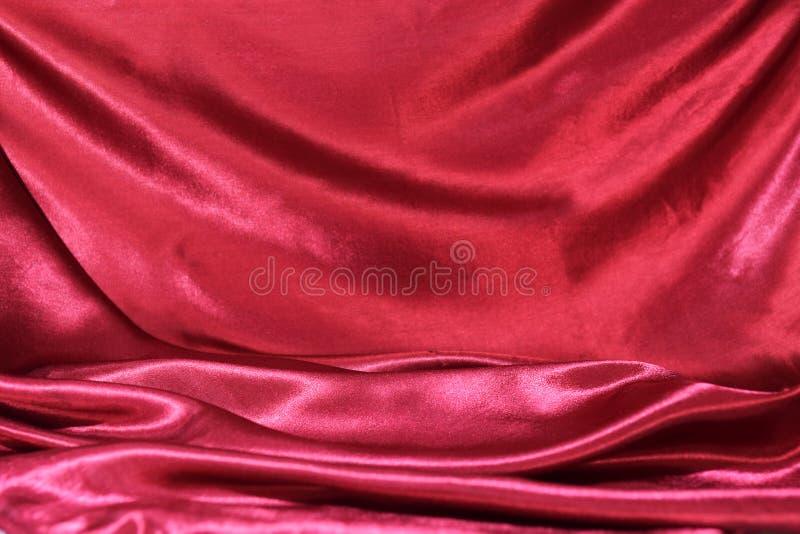 Het kronkelen van vouwen van de stof van donkerrode zijde royalty-vrije stock foto's