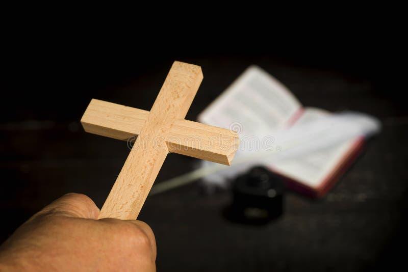 Het kruis hield in de palm van de hand tegen de achtergrond van stock foto