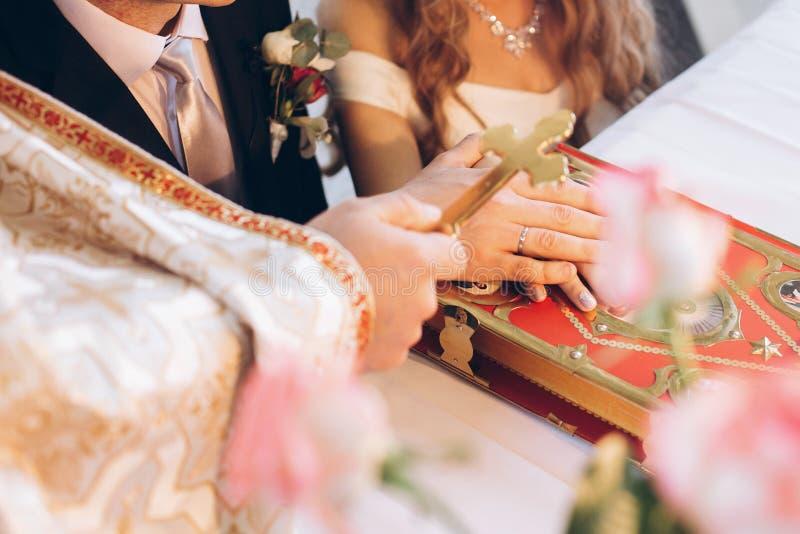 Het kruis van de priesterholding op bruidegom en bruidhand op bijbel bij altaar i stock foto's