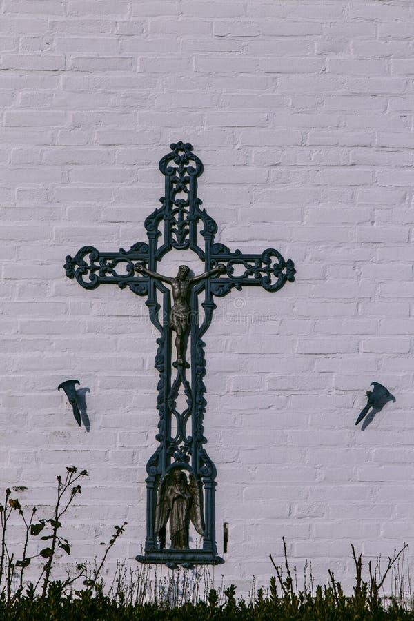 Het kruis van het gietijzergebied tegen een oude landbouwer façade stock afbeelding