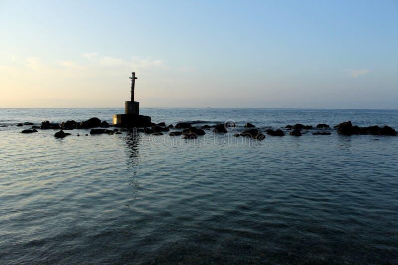 Het kruis vormde steenhoop, oriëntatiepunt of mijlpaal van beton in midden van het overzees wordt gemaakt die stock afbeeldingen