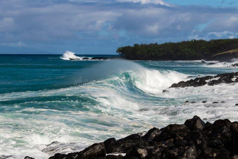 Het krullen golf het slepen het overzeese nevel breken dichtbij kust op Hawaiiaanse kostenstrook van land op achtergrond met rots royalty-vrije stock fotografie