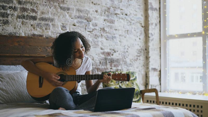 Het krullende Afrikaanse Amerikaanse tienermeisje concentraing leren om gitaar te spelen die laptop computerzitting op bed thuis  stock afbeelding