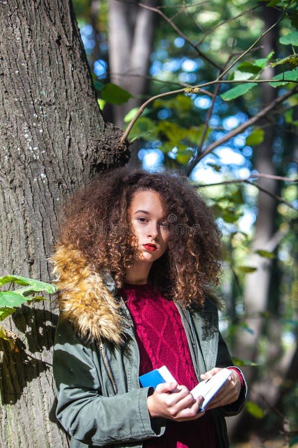 Het krullende boek van de het meisjeslezing van de haartiener in de herfstpark royalty-vrije stock afbeelding