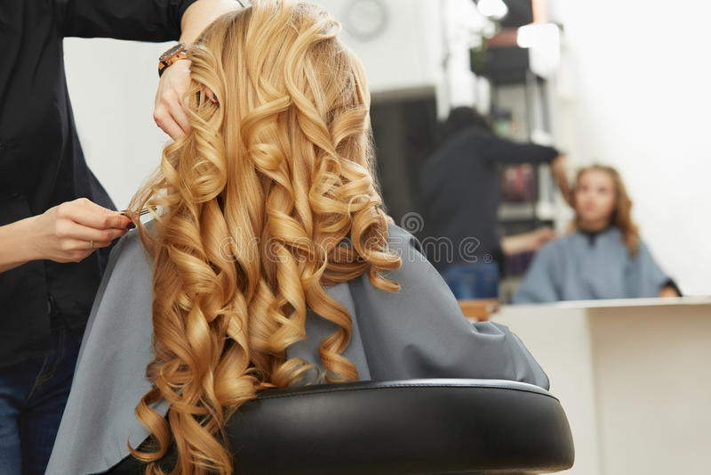 Het krullende haar van de blonde Kapper die kapsel voor jonge vrouw i doen stock fotografie