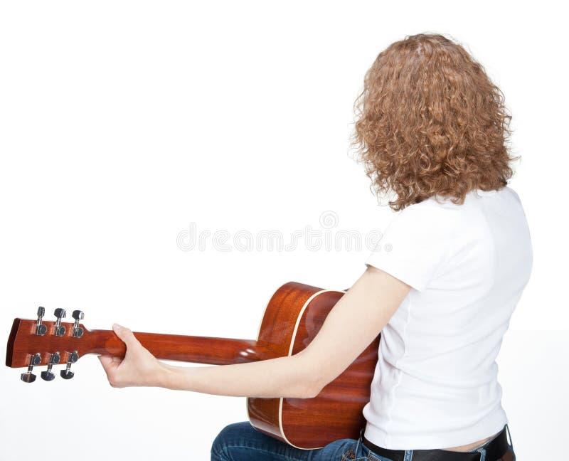 Het krullende jonge vrouw spelen op gitaar stock afbeeldingen