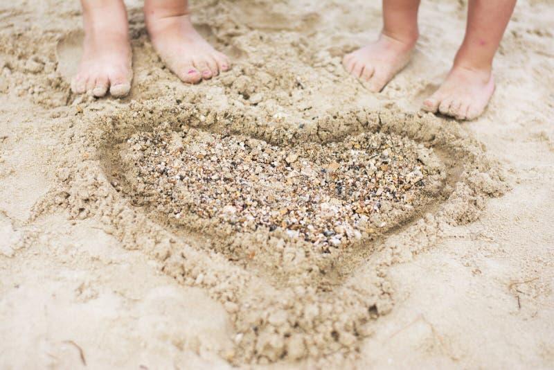 Het krullende kind spelen op strand stock afbeeldingen