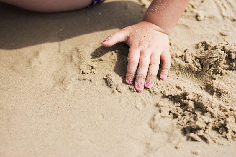 Het krullende kind spelen op strand royalty-vrije stock afbeeldingen