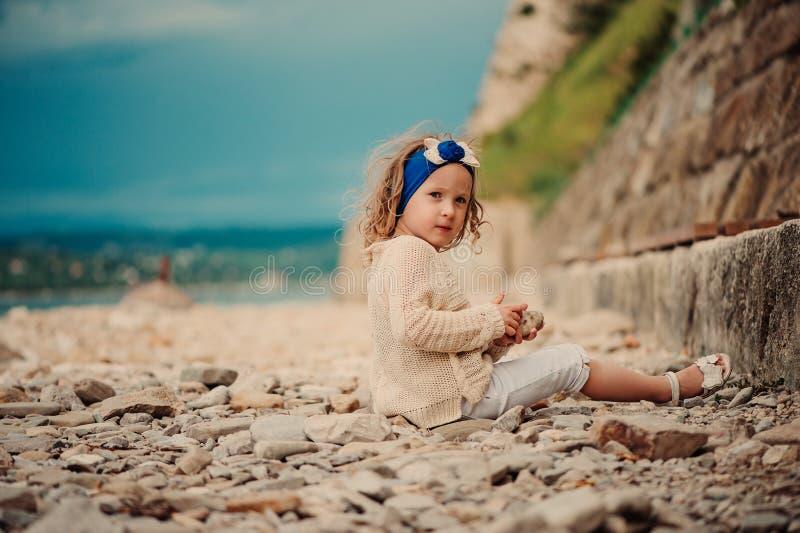 Het krullende kindmeisje spelen met stenen op het strand royalty-vrije stock fotografie