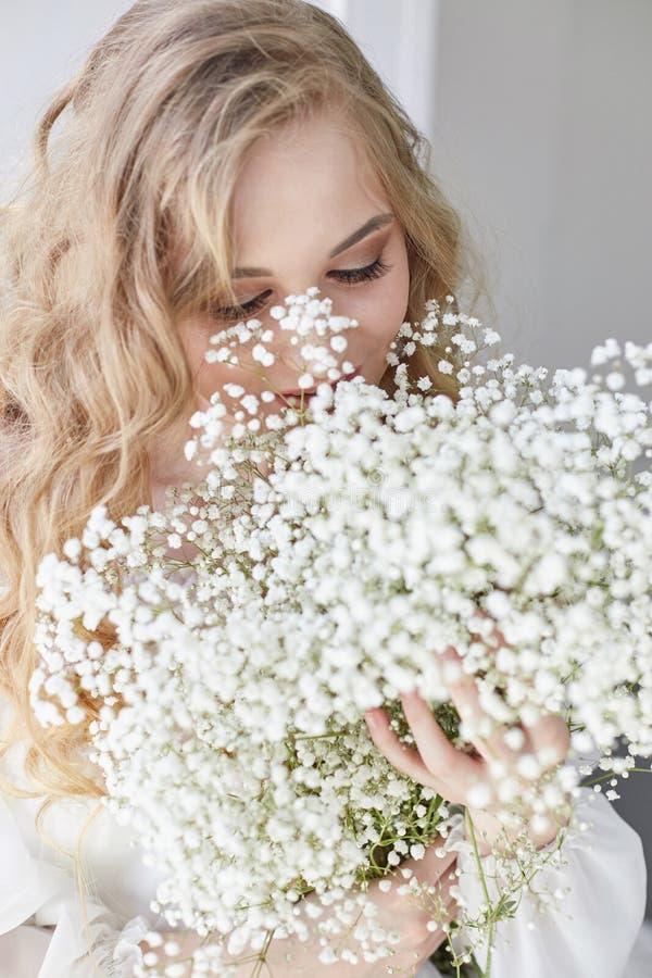 Het krullende romantische blonde kijkt, mooie ogen Witte wildflowers in handen Meisjes witte lichte kleding en krullend haar, por royalty-vrije stock fotografie