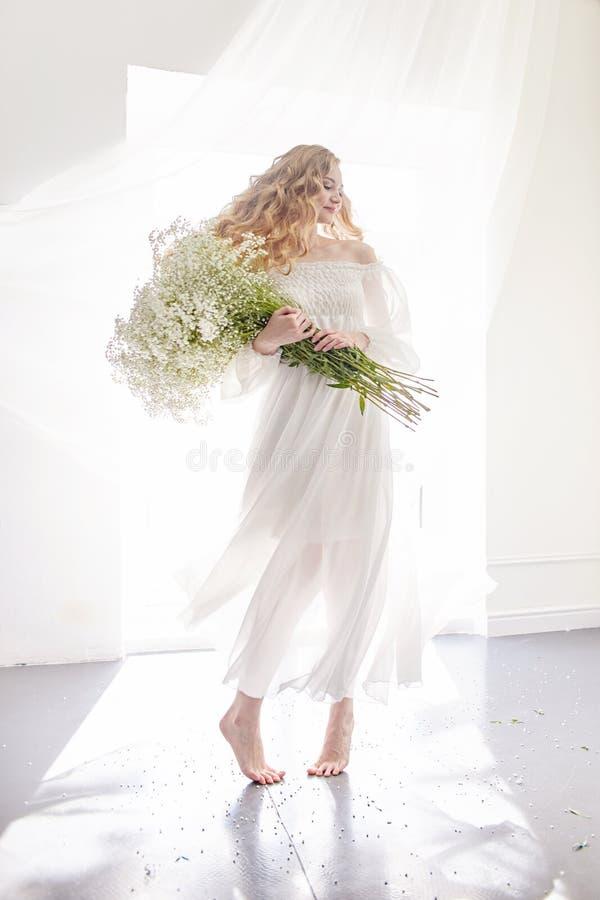 Het krullende romantische blonde kijkt, mooie ogen Witte wildflowers in handen Meisjes witte lichte kleding en krullend haar, por stock fotografie
