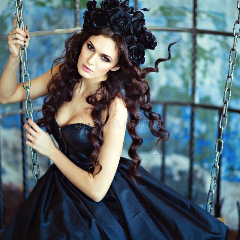 Het krullende sensuele brunette met een kroon van zwarte bloemen zit op Th royalty-vrije stock foto