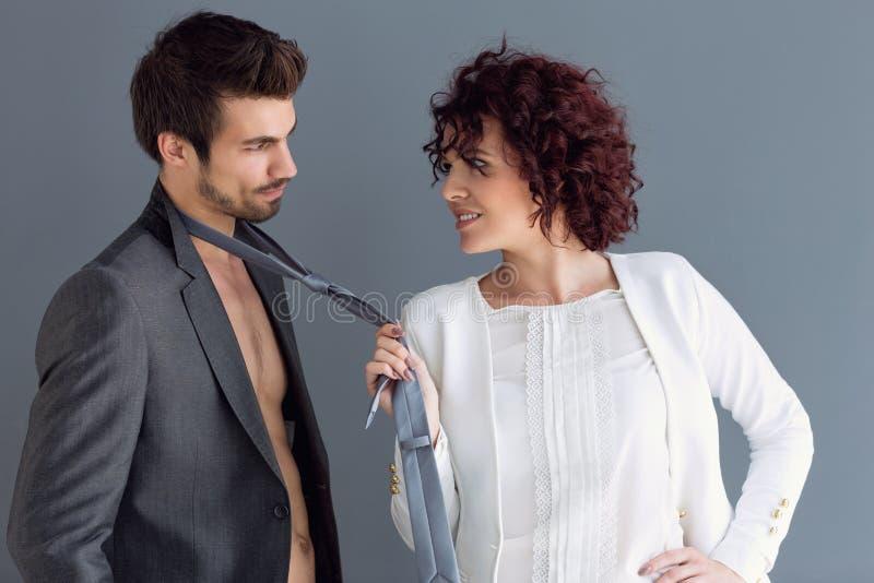 Het krullende vrouw stellen met de mens die zijn band slepen stock afbeeldingen